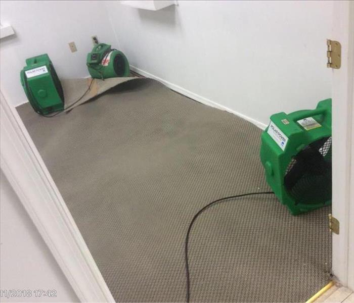Brown carpet with an air mover under the corner