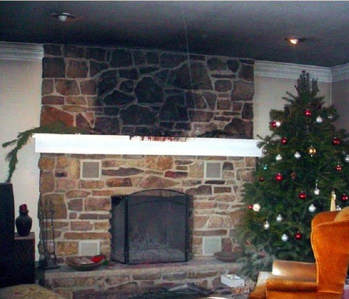 Stone fireplace covered in black soot and ash