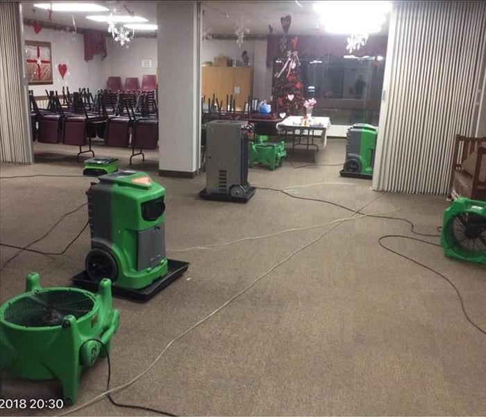 Room with air movers and dehumidifiers spread around