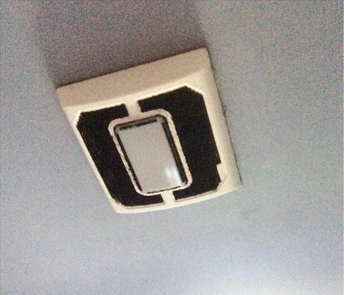 White ceiling exhaust fan with black soot in the vents
