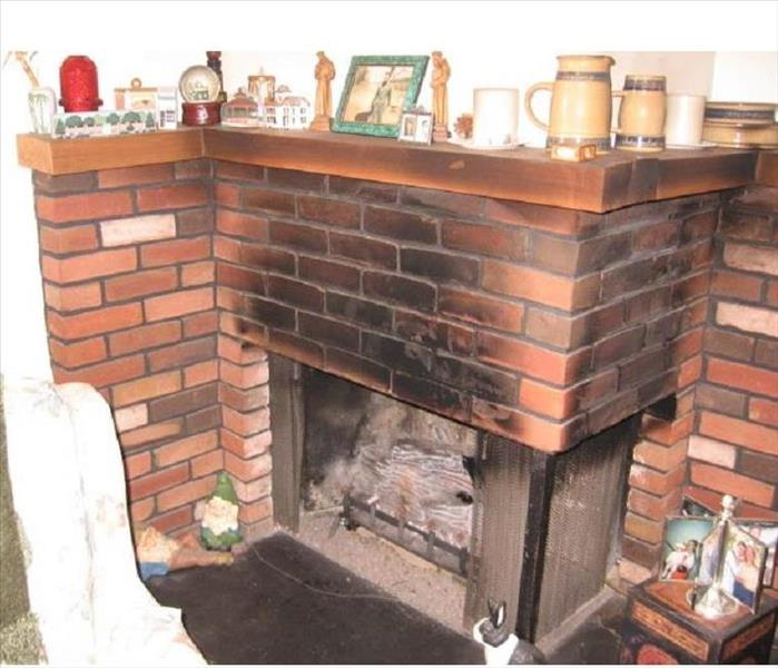 Brick fireplace with black soot rising up towards the chimney
